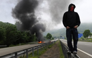 A miner on strike stands in front of a burning barricade on the A-66 motorway, on the first day of a strike to protest the government's spending cuts in the mining sector, in Pola de Lena, near Oviedo, northern Spain, May 23, 2012. Spain's economy is contracting for the second time since late 2009 and four years of stagnation and recession have pushed unemployment above 24 percent, the highest rate in the European Union.   REUTERS/Eloy Alonso
