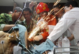 (L-R) Fellow workers, a firefighter and doctors work together to cut steel bars which were pierced through a worker's body during an operation at a hospital in Hangzhou, Zhejiang province, June 12, 2012. The worker was pierced by seven steel bars during his duty at a bridge construction site on Monday afternoon, local media reported. Picture taken June 12, 2012. REUTERS/China Daily (CHINA - Tags: BUSINESS CONSTRUCTION HEALTH TPX IMAGES OF THE DAY) CHINA OUT. NO COMMERCIAL OR EDITORIAL SALES IN CHINA