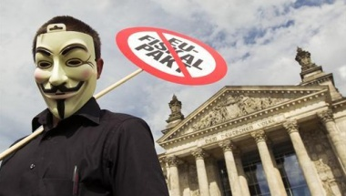 A protester wears a Guy Fawkes mask during a rally against the ratification of a fiscal pact law outside the Reichstag, the seat in the German lower house of parliament, the Bundestag, in Berlin, June 29, 2012. REUTERS/Thomas Peter