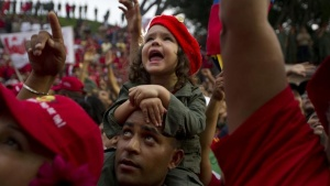 Supporters cheer for Venezuelan President Hugo Chavez at the People's balcony at Miraflores Palace in Caracas April 13, 2012. Chavez commemorated ten years of his return to power after a brief coup who ousted him for two days in 2002. REUTERS/Carlos Garcia Rawlins (VENEZUELA - Tags: POLITICS TPX IMAGES OF THE DAY) - RTR30PC8