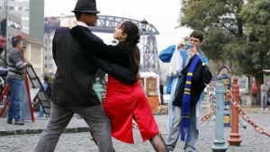 A tourist (L) has his picture taken as he poses with a tango dancer in the neighborhood of La Boca in the Caminito district of Buenos Aires, in this picture taken August 18, 2010.   REUTERS/Marcos Brindicci