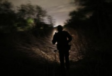 A U.S. Border Patrol agent from the Rio Grande Valley Sector searches the brush and trees at night for a group illegal immigrants who had crossed over the Rio Grande River in Mission, Texas, March 28, 2013. REUTERS/Eric Thayer