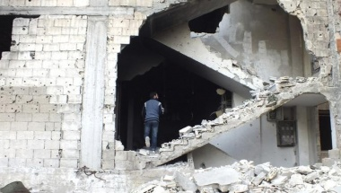 A man is seen on a damaged staircase in Homs, May 19, 2013. REUTERS/Yazen Homsy
