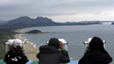 South Koreans look at the North Korean territory (top) through binoculars at an observation post, just south of the demilitarised zone separating the two Koreas, in Goseong, about 330 km (205 miles) northeast of Seoul, May 19, 2013. REUTERS/Lee Jong-kun/Yonhap  