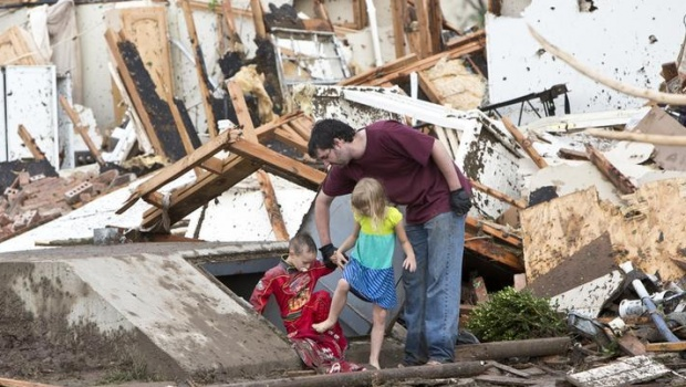 A man and two children walk through debris after a huge tornado struck Moore, Oklahoma, near Oklahoma City, May 20, 2013.  REUTERS/Richard Rowe