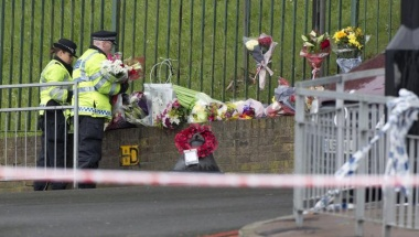Police officers place flowers at the scene of the killing of a British soldier in Woolwich, southeast London May 23, 2013.  REUTERS/Neil Hall
