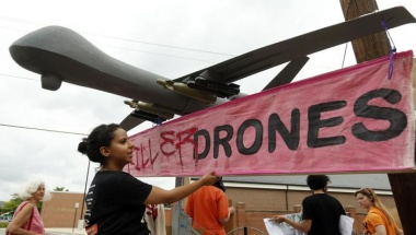 "A demonstrator adjusts a sign reading ""Stop Killer Drones"" hung on a mock drone at the gates of Fort McNair where President Barack Obama spoke at the National Defense University in Washington May 23, 2013. REUTERS/Kevin Lamarque"
