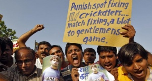 Demonstrators shout slogans as they hold a placard and posters of former India test bowler Shanthakumaran Sreesanth during a protest in Ahmedabad May 16, 2013. REUTERS/Amit Dave/Files
