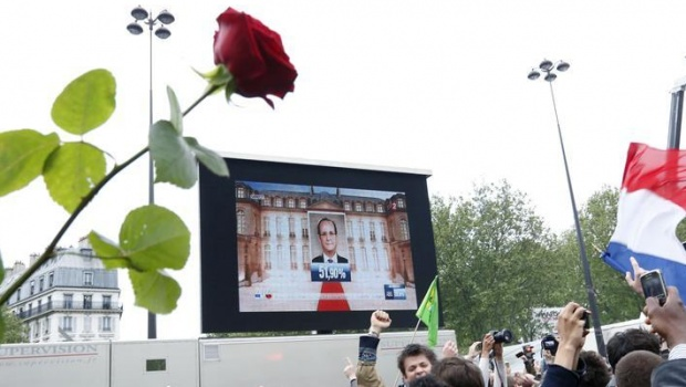 The face of the newly-elected French President Francois Hollande appears on a giant screen to announce the winner of the 2012 French presidential elections as Socialist supporters react at La Bastille square in Paris May 6, 2012. France voted in elections on Sunday and Francois Hollande becomes the nation's first Socialist president  in 17 years, early estimations said.  REUTERS/Pascal Rossignol  (FRANCE - Tags: POLITICS ELECTIONS) - RTR31P7B