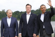 Russia's President Valdimir Putin (L) looks at Britain's Prime Minister David Cameron and U.S. President Barack Obama during a family photo at the G8 Summit, at Lough Erne, near Enniskillen, in Northern Ireland June 18, 2013.  REUTERS/Yves Herman
