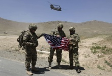 NATO soldiers stand with the U.S. flag as a Chinook helicopter takes off after a security handover ceremony at a military academy outside Kabul June 18, 2013. REUTERS/Omar Sobhani