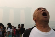 A tourist poses for photos with the Merlion (unseen) in the hazy skyline of Singapore June 20, 2013. REUTERS/Edgar Su