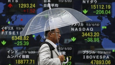 A man holding an umbrella walks past an electronic board displaying Japan's Nikkei average and various countries' stock price index outside a brokerage in Tokyo June 20, 2013. REUTERS/Issei Kato