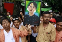 Supporters hold a picture of Myanmar pro-democracy leader Aung San Suu Kyi as they celebrate at her 68th birthday ceremony in front of the party headquarters of National Leage for Democracy in Yangon June 19, 2013.