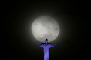 The moon is pictured next to Christ the Redeemer statue ahead the visit of Pope Francis in Rio de Janeiro July 21, 2013. Pope Francis will travel to Brazil on his first international trip as pontiff in July. The main purpose of the trip is for the pope to preside at the Catholic Church's World Day of Youth.    REUTERS/Ricardo Moraes
