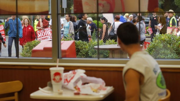 A diner watches strikers marching outside a Wendy's restaurant in Boston, Massachusetts August 29, 2013, as a part of a nationwide fast food workers' strike asking for $15 per hour wages and the right to form unions.   REUTERS/Brian Snyder