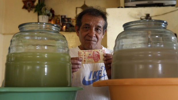 "Jorge, 60, poses for a photograph as he holds $100 Mexicans at ""La antigua Roma"" pulqueria in downtown Mexico City July 24, 2013. Jorge, who suffers from advanced deafness, has worked as a barman at a pulqueria for eleven hours a day for over 30 years and earns eight dollars per day. Jorge's salary does not allow him to rent a house and he lives with the family of his wife on the outskirts of the city from where he travels for two hours to get to work. Pulque is a traditional alcoholic beverage made from the fermented sap of the maguey plant. REUTERS/Edgard Garrido"
