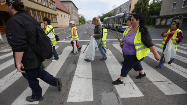 Hungarian public worker Gabriella Bundi (in purple), 44, crosses the street with her colleagues in Debrecen, 240 km (149 miles) east of Budapest, May 29, 2013. Gabriella, who has been unemployed for three years, takes temporary menial work mandated by the government in exchange for unemployment benefits. He husband works odd jobs. From this and meagre social benefits, she and her husband bring home about 250,000 forints, or $1,200 per month. The couple have five children, a son-in-law and a grandchild living in their home.  REUTERS/Laszlo Balogh
