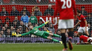 Manchester United's goalkeeper David de Gea dives for the ball as Newcastle United's Yohan Cabaye (unseen) scores a goal during their English Premier League soccer match at Old Trafford in Manchester, northern England December 7, 2013. REUTERS/Darren Staples