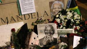 Tributes and flowers accumulate at the base of a statue of South Africa's former president Nelson Mandela at Parliament Square in London December 6, 2013. REUTERS/Suzanne Plunkett