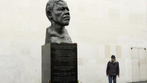 A man looks at flowers left at a sculpture of South Africa's former president Nelson Mandela on the South Bank in central London December 8, 2013. REUTERS/Olivia Harris