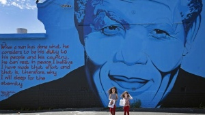 India Harris, age eight, and her sister Kitty, five, stand in front of a Nelson Mandela wall mural shortly after laying bouquets of flowers for the late former South African president in Cape Town December 7, 2013. REUTERS/Mark Wessels