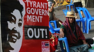 An anti-government protester rests next to a banner during a rally outside the Government House in Bangkok December 12, 2013. REUTERS/Chaiwat Subprasom