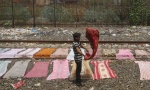 A laundryman dries clothes in middle of railway tracks at a suburban station in Mumbai September 11, 2013. REUTERS/Danish Siddiqui/Files