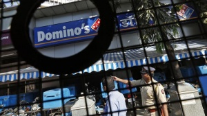 A policeman (R) talks to an employee of a Domino's Pizza outlet after it was ransacked by activists of the Republican Party of India (RPI) in a Mumbai suburb December 20, 2013. REUTERS/Mansi Thapliyal