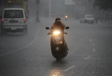 A woman rides a scooter during heavy rainfall in Chandigarh July 10, 2012. REUTERS/Ajay Verma/Files
