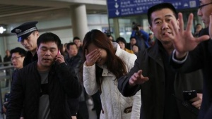 A relative (C, in white) of a passenger onboard Malaysia Airlines flight MH370, covers her face as she cries at the Beijing Capital International Airport in Beijing March 8, 2014. REUTERS/Kim Kyung-Hoon