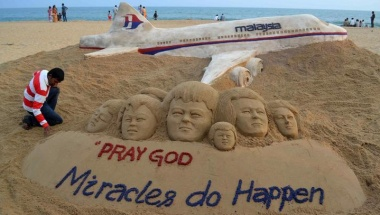 Indian sand artist Sudarshan Patnaik applies the final touches to a sand art sculpture he created wishing for the well being of the passengers of Malaysian Airlines flight MH370, on a beach in Puri, in the eastern Indian state of Odisha, March 9, 2014. REUTERS/Stringer