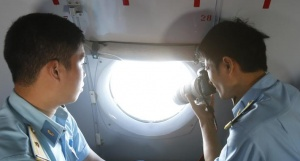 A military personnel takes photos from the window of an aircraft belonging to the Vietnamese airforce during a search and rescue mission off Vietnam's Tho Chu island March 10, 2014. REUTERS/Kham
