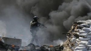 A Ukrainian security force officer is deployed at a checkpoint set on fire and left by pro-Russian separatists near Slaviansk April 24, 2014. REUTERS/Gleb Garanich