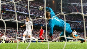 Real Madrid's Karim Benzema (L) scores against Bayern Munich's goalkeeper Manuel Neuer during their Champions League semi-final first leg soccer match at Santiago Bernabeu stadium in Madrid April 23, 2014. REUTERS/Darren Staples