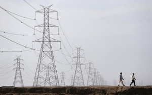 Men walk past electric pylons in Little Rann of Kutch in the western Indian state of Gujarat March 2, 2014. REUTERS/Ahmad Masood/Files