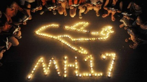 College students gather around candles forming the shape of an airplane, during a candlelight vigil for victims of the downed Malaysia Airlines Flight MH17, at a university in Yangzhou, Jiangsu province July 19, 2014. REUTERS/Stringer