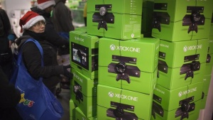 A woman walks past a pile of XBOX One video game consoles at a store in New York November 28, 2013. REUTERS/Carlo Allegri/Files