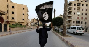 A member loyal to the Islamic State in Iraq and the Levant (ISIL) waves an ISIL flag in Raqqa June 29, 2014. REUTERS/Stringer/Files
