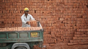 A worker loads bricks onto a vehicle near a construction site of a residential complex in New Delhi May 30, 2014. REUTERS/Anindito Mukherjee/Files