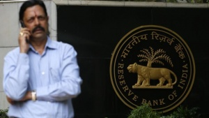 A man speaks on his mobile phone in front of the Reserve Bank of India (RBI) seal at the RBI headquarters in Mumbai July 30, 2013. REUTERS/Vivek Prakash/Files