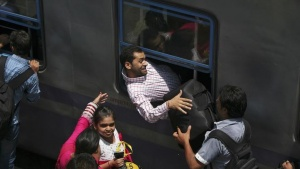 A passenger squeezes in through the window of a stationary train at a railway station in Jammu July 8, 2014. REUTERS/Mukesh Gupta/Files