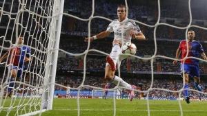 Real Madrid's Gareth Bale (C) kicks to score next to FC Basel's Walter Samuel (R) and Marek Suchy during their Champions League soccer match at Santiago Bernabeu stadium in Madrid September 16, 2014. REUTERS/Juan Medina