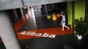 An employee walks past a logo of Alibaba (China) Technology Co. Ltd during a media tour organized by government officials at its headquarters on the outskirts of Hangzhou, Zhejiang province June 20, 2012. REUTERS/Carlos Barria