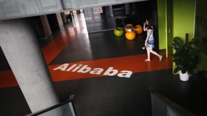 An employee walks past a logo of Alibaba (China) Technology Co. Ltd during a media tour organized by government officials at its headquarters on the outskirts of Hangzhou, Zhejiang province June 20, 2012. REUTERS/Carlos Barria/Files