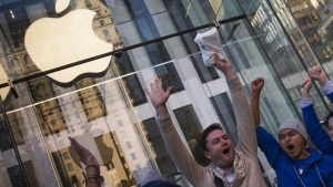 Local resident Andreas Gibson celebrates after being the first to exit the Fifth Avenue store after purchasing an iPhone 6 on the first day of sales in Manhattan, New York September 19, 2014. \ REUTERS/Adrees Latif