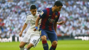 "Real Madrid's James Rodriguez (L) challenges Barcelona's Luis Suarez during their Spanish first division ""Clasico"" soccer match at the Santiago Bernabeu stadium in Madrid October 25, 2014. REUTERS/Juan Medina"