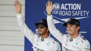 Mercedes Formula One driver Nico Rosberg (R) of Germany standing next to team mate Lewis Hamilton of Britain, celebrates after winning pole position in the qualifying session of the Japanese F1 Grand Prix at the Suzuka Circuit October 4, 2014. REUTERS/Yuya Shino/Files