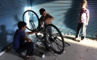Children use a bicycle to recharge a battery in order to use it to power a light source in Douma, eastern Ghouta, September 21, 2013. REUTERS/Bassam Khabieh/Files