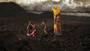Labourers rest as a boy playfully shovels coal at a yard in Ahmedabad November 20, 2014. REUTERS/Amit Dave